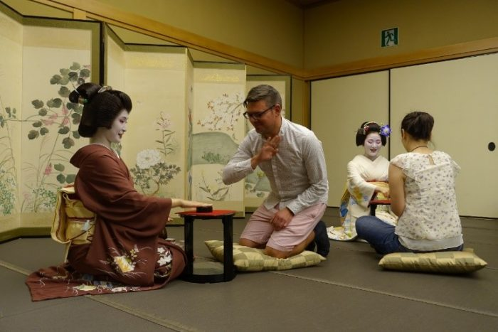 A geiko (left) and maiko (right) play games with fellows.